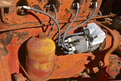 Spark plug wiring of an old orange tractor. Spark plugs, distributor, oil filter and engine block of an old orange tractorSpark plugs, distributor, oil filter Royalty Free Stock Photos