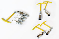 Spark plug wrenches. Yellow spark plug wrenches and spark plugs on a white background Royalty Free Stock Photography