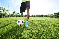 Sparka Soccerball på fält Royaltyfria Bilder