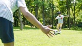 Sparkande fotboll för asiatisk pojke in mot hans fader som målvårdare utomhus i sommar i ultrarapid arkivfilmer