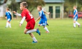 Sparkande fotboll för pojke på sportfältet Royaltyfria Bilder