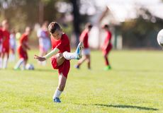 Sparkande fotboll för pojke på sportfältet Royaltyfri Fotografi