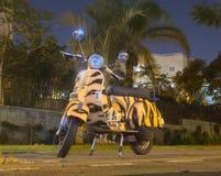 Sparkcykel som vespaen som parkeras under lyktan på natten Royaltyfri Bild