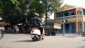 Sparkcyklar, bilar, trafik, turister och folk på daggatorna av Hoi An, Vietnam lager videofilmer
