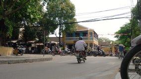 Sparkcyklar, bilar, trafik, turister och folk på daggatorna av Hoi An, Vietnam stock video