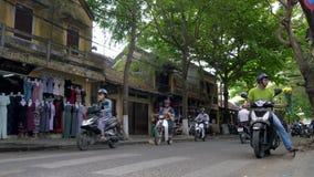 Sparkcyklar, bilar, trafik, turister och folk på daggatorna av Hoi An, Vietnam arkivfilmer