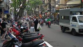Sparkcyklar, bilar, trafik, turister och folk på de gamla fjärdedelgatorna av huvudstaden, Hanoi, Vietnam lager videofilmer