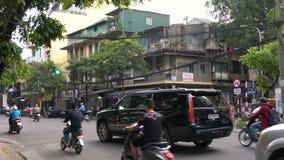 Sparkcyklar, bilar, trafik, turister och folk på de gamla fjärdedelgatorna av huvudstaden, Hanoi, Vietnam stock video