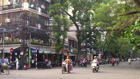 Sparkcyklar, motorcyklar, bilar, trafik, turister och folk på de gamla fjärdedelgatorna av huvudstaden, Hanoi, Vietnam stock video