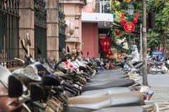 Sparkcyklar och kommunistiskt propagandasymbol i Hanoi, Vietnam royaltyfri foto