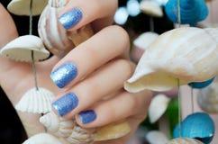 Sparkle beautiful blue manicure. On a background of sea shells stock photo