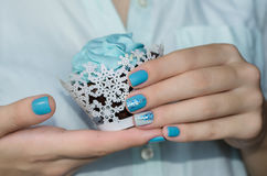 Sparkle beautiful blue manicure. Cupcake in woman hand with sparkle blue manicure stock photography