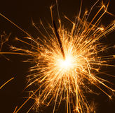 Sparkle. Close up of a burning sparkler on a dark background stock images