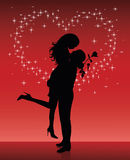 Sparkle heart. Silhouette of a man lifting a woman up in his hands on a red background with sparkles in shape of a heart Royalty Free Stock Photo