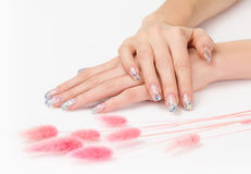 Sparkle manicure and pink decoration. Sparkle gel nails and pink decoration spikes isolated on white Royalty Free Stock Photography