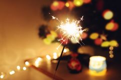 Sparkle stick. With lights and christmas tree on the background Stock Photos