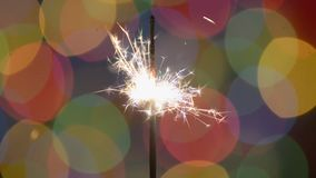 Sparkler πέρα από το υπόβαθρο Χριστουγέννων με τα θολωμένα φω'τα HD χρώματος απόθεμα βίντεο