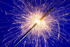 Sparkler against blue background. Royalty Free Stock Photography