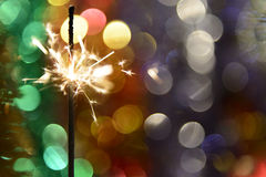 sparkler on a background of blurred lights Royalty Free Stock Photography
