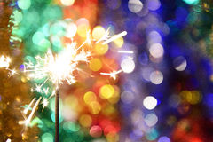 Sparkler on a background of blurred lights Royalty Free Stock Images