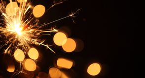 Sparkler background. Close-up of sparkler on Christmas lights background Stock Photography