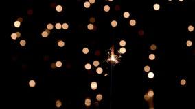 Sparkler burning in front of ambient lights. Gun powder sparks shot against bokeh lights background. 4k stock video