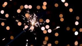 Sparkler burning in front of ambient lights in slow motion. Sparkler burning in front of ambient lights. Gun powder sparks shot against bokeh lights background stock footage