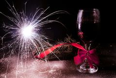 Sparkler and decorated wine glass for new year on wooden desk and snow. Sparkler burning and red decorated wine glass with tie bow for new year on decorated Royalty Free Stock Photos