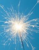 Sparkler. Close up of a burning sparkler on a blue background royalty free stock image