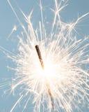 Sparkler. Close up of a burning sparkler over a light blue background Royalty Free Stock Image