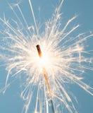 Sparkler. Close up of a burning sparkler over a light blue background Stock Images