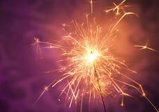 Sparkler. Close up of a burning sparkler on a vibrant background stock photo