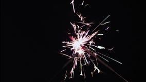 Sparkler defocus closeup. Defocused sparkler on black background stock footage