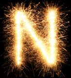 Sparkler firework light alphabet N on black. Background royalty free stock images