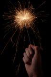 Sparkler in hand. Hand holding a sparkler on black background Stock Images