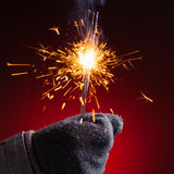 Sparkler in hand mitten. Close-up view, red background stock image