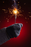 Sparkler in hand mitten Royalty Free Stock Image