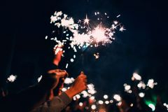 Sparkler in hands of happy people on holiday with sparks. On dark background Royalty Free Stock Image