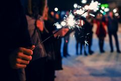 Sparkler in hands of people on holiday with sparks. On dark background Royalty Free Stock Images