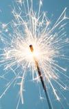 Sparkler Macro. Close up of a burning sparkler on a blue background stock photos