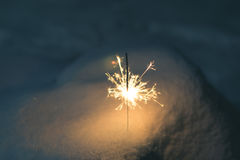 Sparkler in the snow in the evening Stock Image