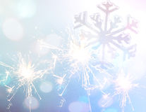 Sparkler with snowflake sign on blue glitter christmas background Royalty Free Stock Photography