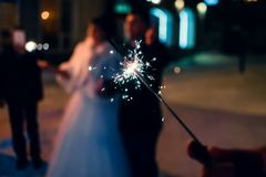 Sparkler with sparks in the hand of man on holiday on blurry background. Of people Stock Photography