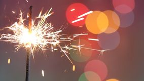 Sparkler stick on abstract colorful christmas new year party birthday background. Closeup stock video footage