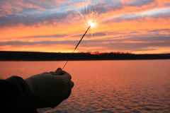 Sparkler on sunset background. Gloved hand holding a burning sparkler on sunset background Royalty Free Stock Images