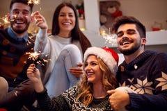 Sparklers-φίλοι Χριστουγέννων που απολαμβάνουν το κόμμα στα Χριστούγεννα Στοκ Εικόνες