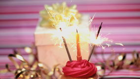 Sparklers on a birthday cupcake with gift Royalty Free Stock Photography