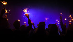 Sparklers burn in hands, night party. Sparklers burn in hands over dark blue background, holidays night party photo with soft selective focus Royalty Free Stock Image