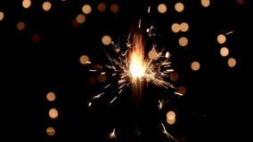 Sparklers burning in front of ambient lights in slow motion. Sparklers burning in front of ambient lights. Gun powder sparks shot against bokeh lights background stock video
