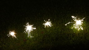 Sparklers in the Grass. Four burning sparklers in the grass at night Stock Photos